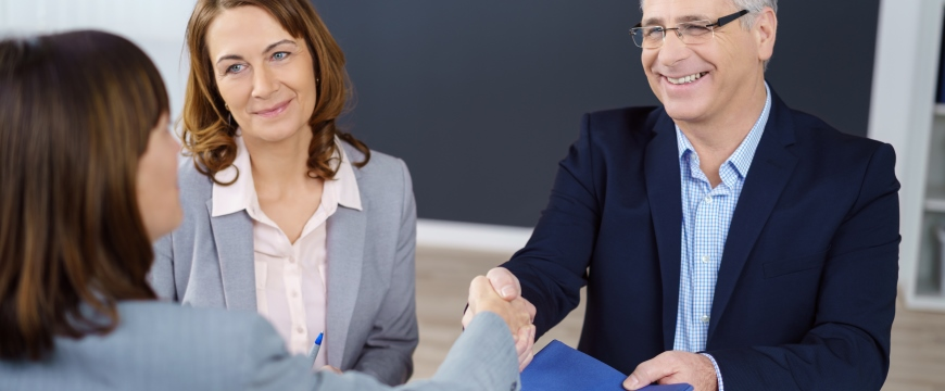 Banker shaking hands with couple