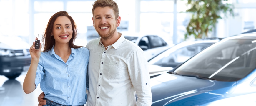 Auto Loans, Young couple with car keys in hand and vehicles pictured in the background