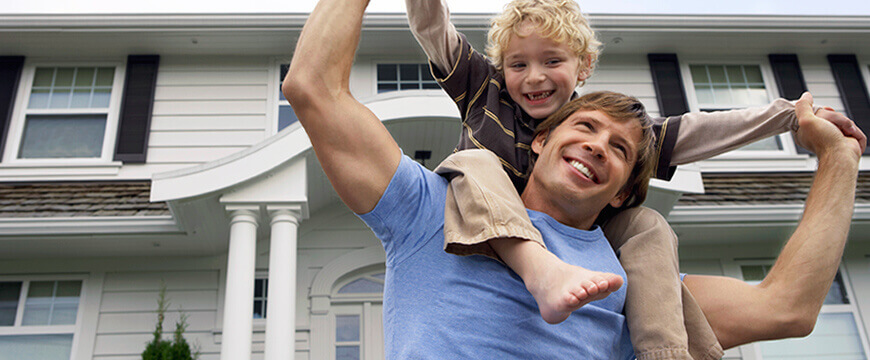Mortgage Image - happy man with a child on his shoulders in front of a house