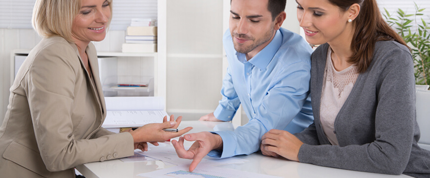 Personal Loans, a young man and woman visiting with bankers pointing at documents